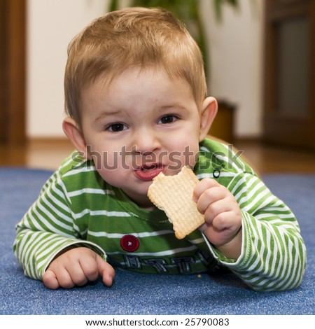 A portrait of a baby eating a biscuit