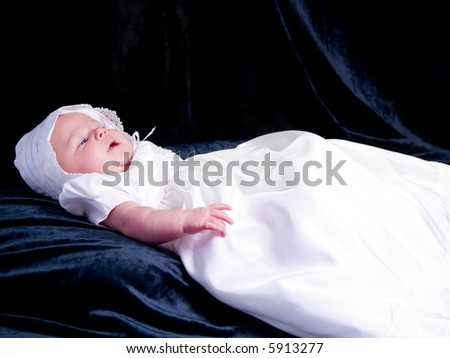 A portrait of a baby girl in a christening dress on a dark background. This photo has a shallow depth of field and the focus is on her right eye.