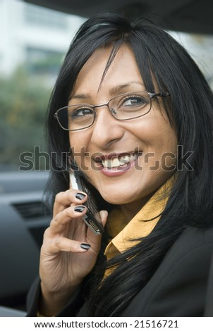 A portrait of a beautiful asian businesswoman enjoying a friendly chat on her cellphone while sitting in her car - stock photo