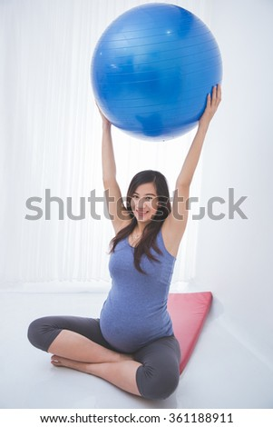 A portrait of a beautiful asian pregnant woman doing exercise with a yoga ball on yoga mat, smiling