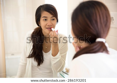 A portrait of a Beautiful asian woman putting make-up on, applying lipstick on her lips - stock photo