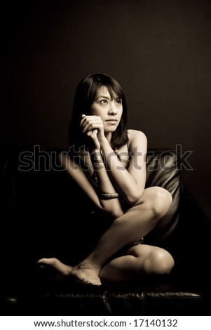 A portrait of a beautiful asian woman sitting on a couch