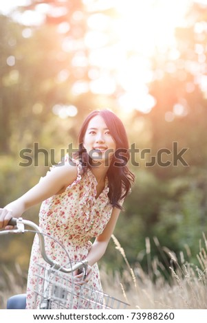 A portrait of a beautiful asian woman with a bicycle outdoor - stock photo