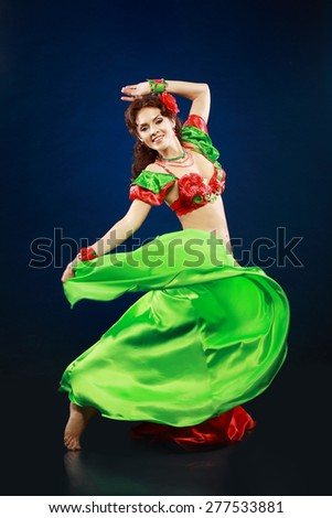 A portrait of a beautiful belly dancer over dark background - stock photo