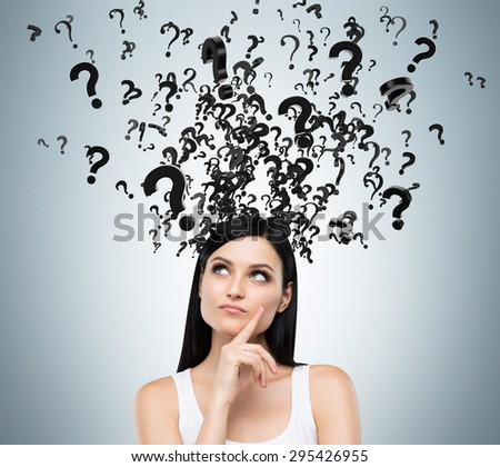 A portrait of a beautiful brunette with questioning expression and question marks above her head. - stock photo