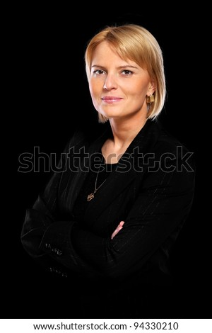 A portrait of a beautiful confident woman standing over black background - stock photo
