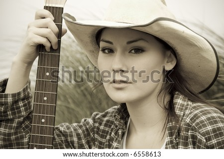 A portrait of a beautiful cowgirl with a guitar in sepia tone - stock photo
