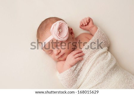 A portrait of a beautiful, 12 day old newborn baby girl wearing a light pink flower headband. She is swaddled and sleeping on her back on a cream colored blanket.  - stock photo