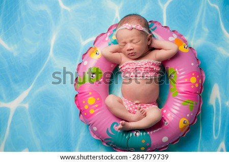 A portrait of a beautiful eleven day old baby girl wearing a pink polka dot bikini. She is sleeping on a pink, inflatable swim ring. - stock photo