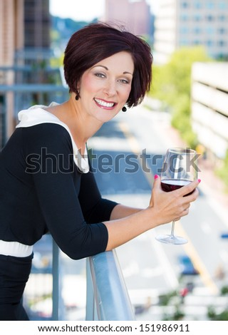 A portrait of a beautiful female, businesswoman relaxing on a balcony on a sunny summer day,drinking red wine, isolated on a background of city buildings and green trees. Urban corporate lifestyle