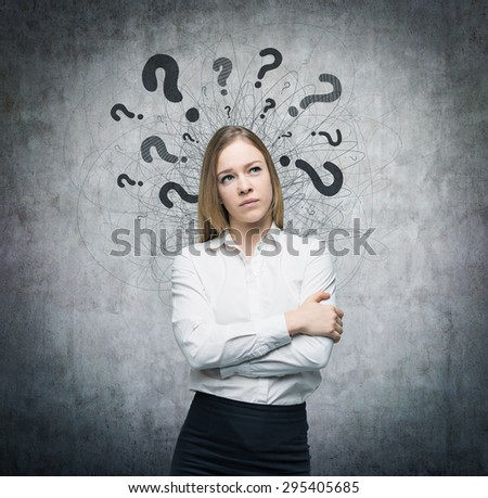 A portrait of a beautiful lady with questioning expression and question marks above her head. Concrete background. - stock photo