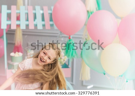 A portrait of a beautiful little girl laughs and jumps in a studio decorated many color balloons - stock photo