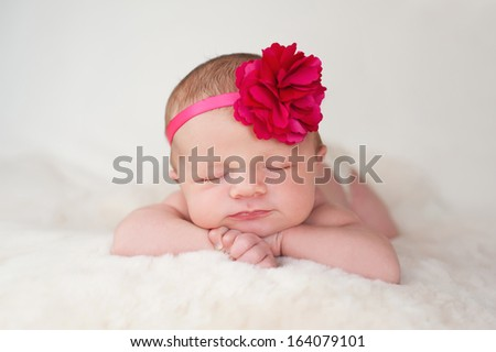 A portrait of a beautiful newborn baby girl wearing a hot pink flower headband. She is sleeping on a cream colored sheepskin rug.  - stock photo