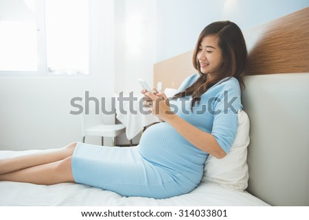 A portrait of a beautiful pregnant woman using mobile phone in her bedroom - stock photo