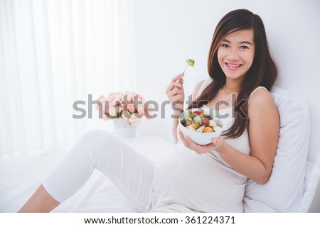 A portrait of a Beautiful pregnant woman with a bowl of fruit, ready to eat - stock photo