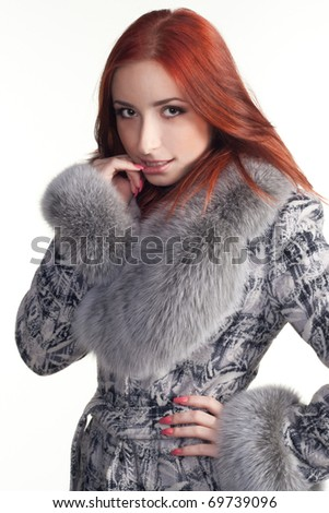 A portrait of a beautiful redhead woman in grey coat - stock photo