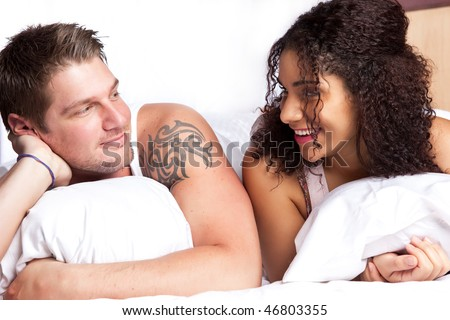 A portrait of a beautiful romantic interracial couple in love lying down on the bed - stock photo