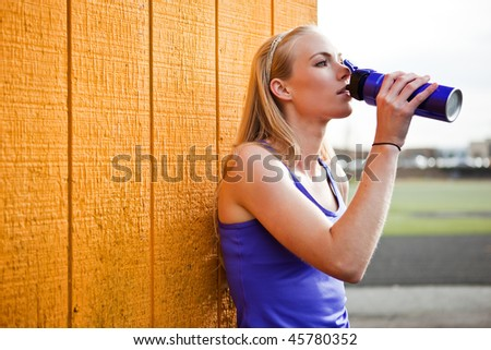A portrait of a beautiful sporty caucasian woman  drinking water - stock photo