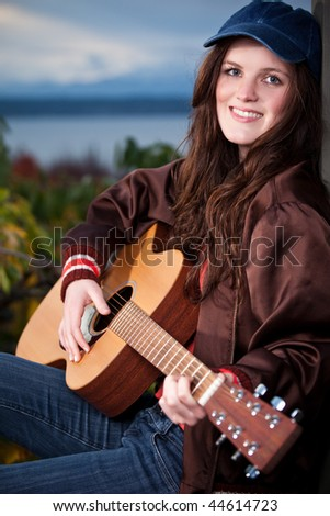 A portrait of a beautiful teenager playing guitar - stock photo