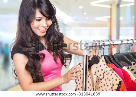 A portrait of a beautiful woman choosing clothes in a store