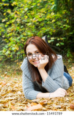 A portrait of a beautiful young caucasian girl lying down on the ground in fall season