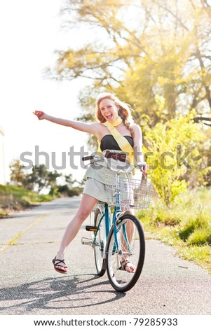 A portrait of a beautiful young Caucasian woman riding her bike outdoor - stock photo