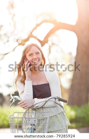 A portrait of a beautiful young Caucasian woman talking on the phone outdoor