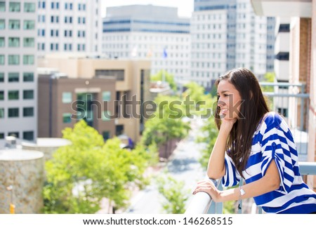 A portrait of a beautiful young female relaxing on a balcony on a sunny summer day, in her new apartment, background of a city scenery and green trees. Urban lifestyle.  - stock photo