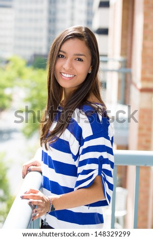 A portrait of a beautiful young female relaxing on a balcony on a sunny summer day, in her new apartment, background of a city scenery and green trees. Urban lifestyle.