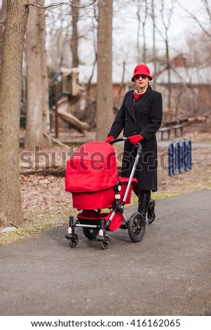 A portrait of a beautiful young mother. An attractive young mother in a black coat and a retro style red hat strolls with a baby carriage at a public park.