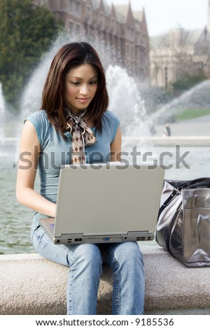 A portrait of a beautiful young woman working on her laptop outdoor - stock photo