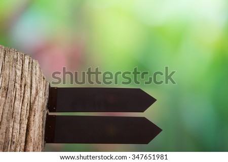 A portrait of a blank billboard or information sign, for advertisement with green blurred nature background.