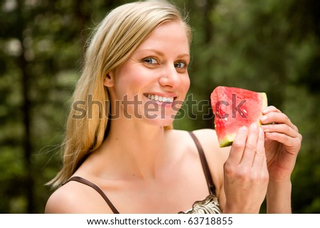 A portrait of a blonde woman eating a watermelon