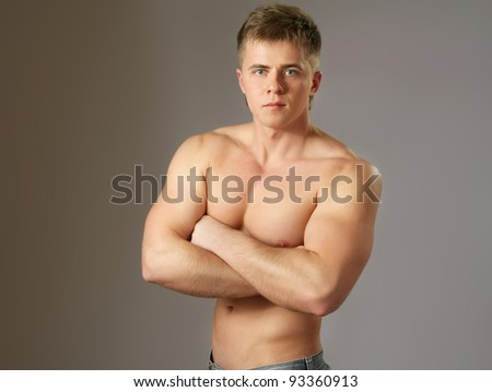 A portrait of a brawny handsome guy with folded arms, isolated on brown background - stock photo