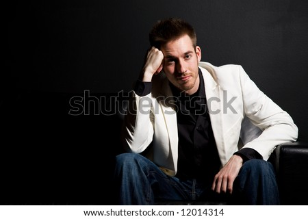A portrait of a casual businessman sitting on a couch - stock photo