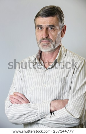 A portrait of a casual middle aged man in striped shirt,  A portrait of a confident senior man standing with his arms crossed  - stock photo