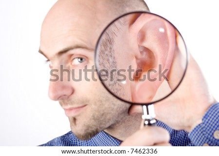 A portrait of a Caucasian adult male on a white background holding a magnifying glass to his ear to indicate that he is listening. - stock photo