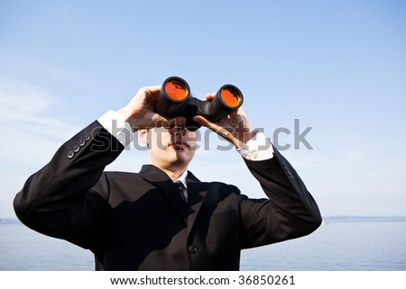 A portrait of a caucasian businessman looking through binoculars  outdoor - stock photo