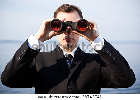 A portrait of a caucasian businessman looking through binoculars  outdoor - stock photo