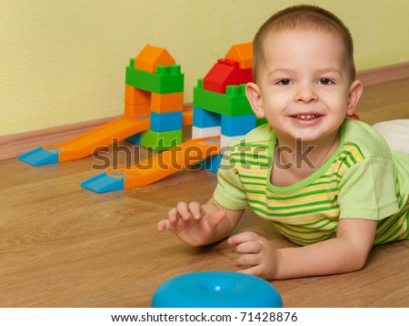 A portrait of a cheerful little kid lying on the wooden floor - stock photo