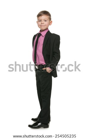 A portrait of a confident little boy in a black suit on the white background - stock photo