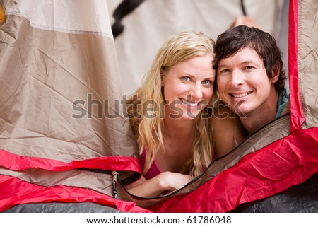 A portrait of a couple smiling in a tent