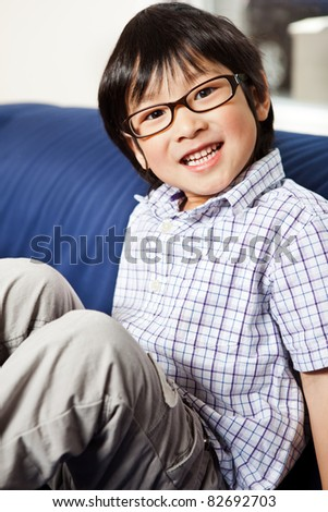 A portrait of a cute asian boy sitting on a sofa at home - stock photo