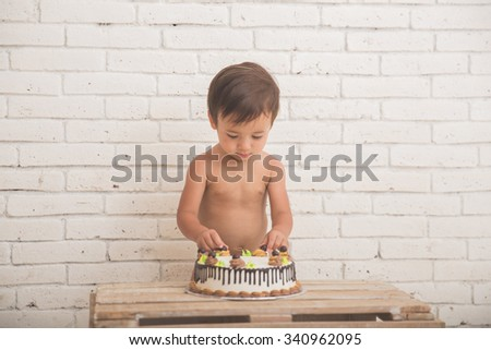 A portrait of a cute caucasian boy playing with his birthday cake