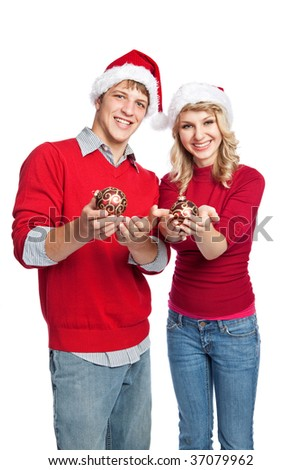 A portrait of a cute caucasian christmas couple holding a christmas ornament