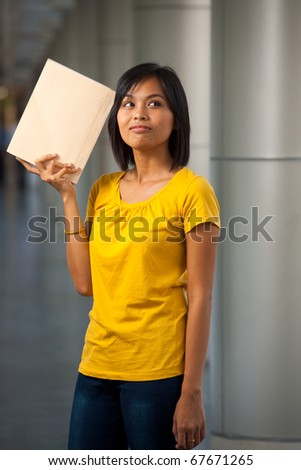 A portrait of a cute college student thinking with a book against her head on a modern university campus.  Young female Asian Thai model late teens, early 20s of Chinese descent.