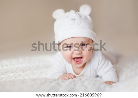 A portrait of a cute funny newborn baby in a white like a bear cub hat lying on its stomach and laughing - stock photo