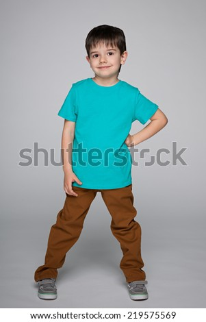 A portrait of a cute little boy in the blue shirt on the gray background