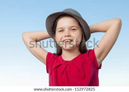 A portrait of a cute little girl, she is standing outside, wearing a hat and a red shirt against a blue sky, her arms are crossed behind her head, she looks relaxed and very happy - stock photo