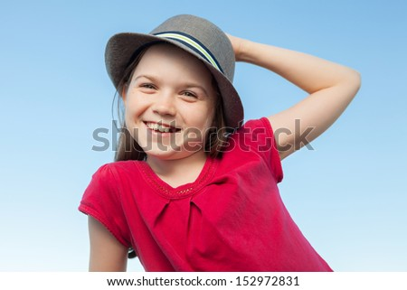 A portrait of a cute little girl, she is standing outside, wearing a hat and a red shirt against a blue sky,she is smiling into the camera - stock photo